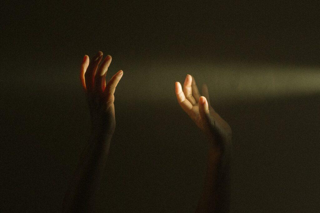 Mains levantadas recebendo um raio de luz.