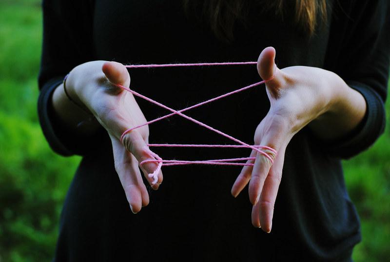 Mans nas que se entrelaça um fio de lam rosa formando uma rede.